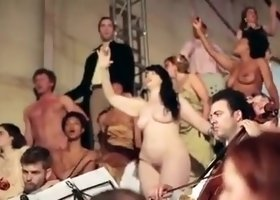 Partly nude opera production with lots of bodies on a stage