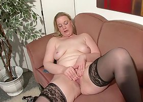 Solo chubby woman in stockings stimulating her cunt with a dildo