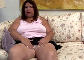 Obese lady plays with a pink dildo while moaning softly