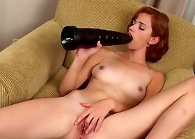 Skinny redhead bitch sucks a huge dildo before poking it in her vag